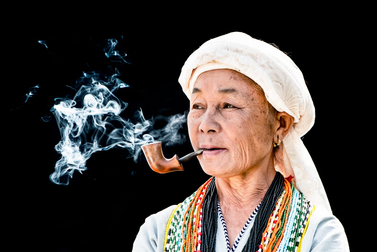 Karen woman smoking a pipe against a black background