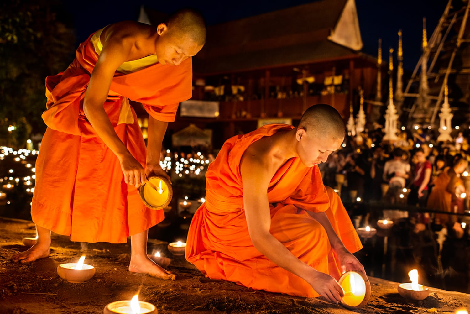 Young monks light candles during the Macha Pucha celebration at at Wat Pan Tao, Chiang Mai, Thailand, Asia.